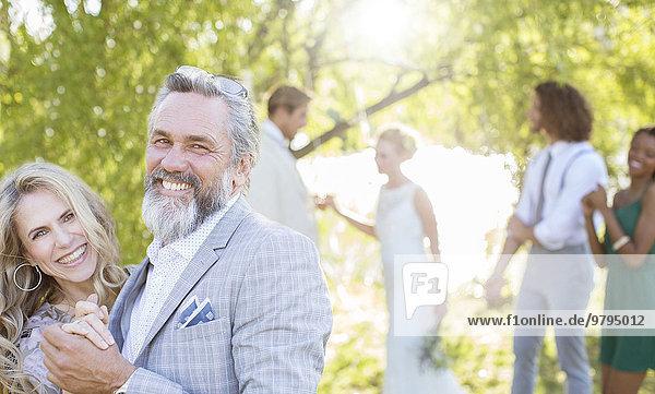 Ehrenmutter tanzt mit Trauzeugen bei der Hochzeitsfeier im Hausgarten