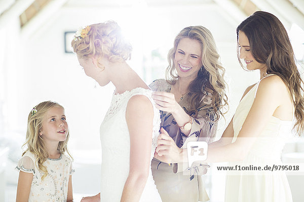 Matron of honor and bridesmaid helping bride with dressing in domestic room