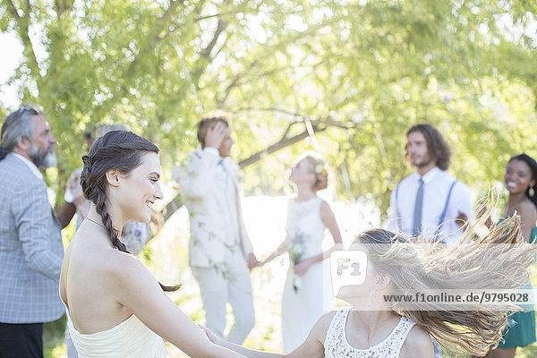 Brautjungfer und Mädchen tanzen bei der Hochzeitsfeier im Hausgarten