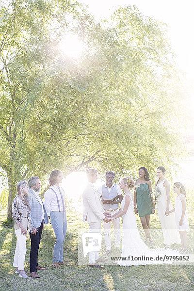 Junges Paar und Gäste bei der Trauung im Hausgarten