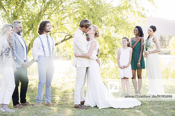 Junges Paar umarmt und küsst sich während der Hochzeitszeremonie im Hausgarten