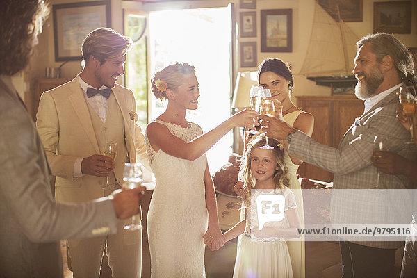 Junges Paar und Gäste toasten mit Champagner bei der Hochzeitsfeier im heimischen Zimmer