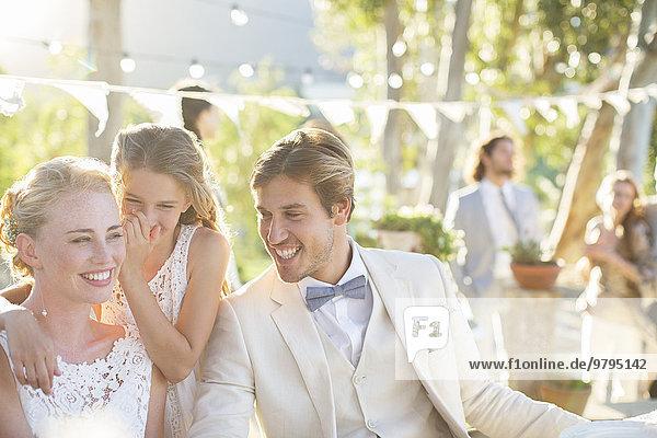 Brautjungfer flüstert während des Hochzeitsempfangs im Hausgarten ins Ohr.