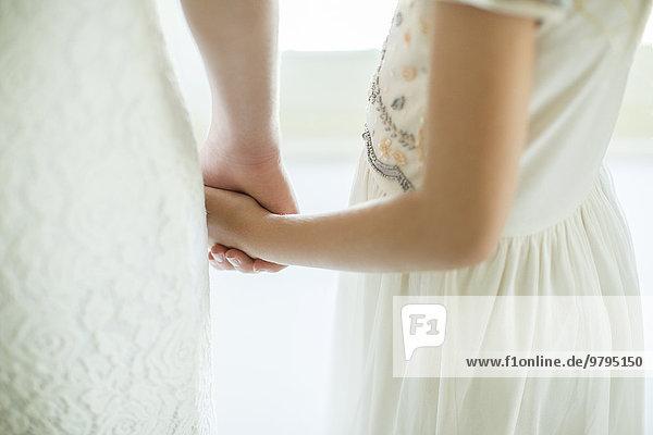 Braut hält Brautjungfernhand im Wohnzimmer