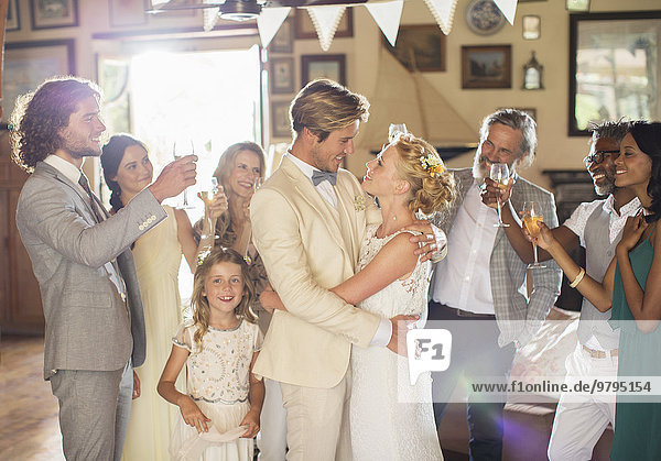 Bräutigam umarmt Braut bei der Hochzeitsfeier im häuslichen Raum