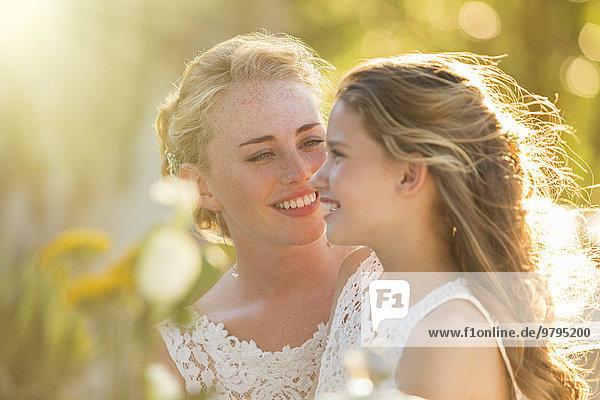 Braut im Gespräch mit Brautjungfer im Hausgarten