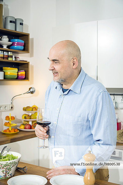 Senior man holding glass of red wine in kitchen