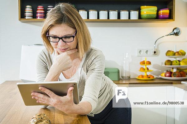 Senior Senioren benutzen Frau Computer Küche Tablet PC