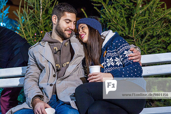 Young couple drinking punch at Christmas Market