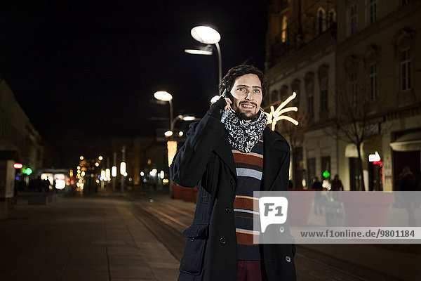 Portrait of young man using phone in city