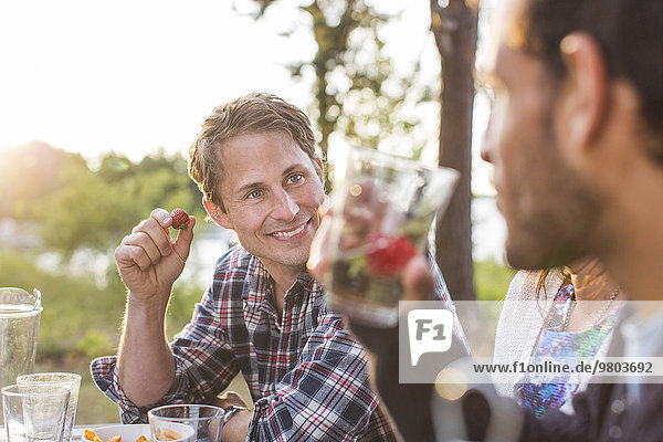 Smiling man having lunch with friends during picnic