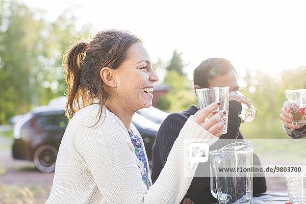 Glückliche Frau beim Trinken mit Freunden auf der Gartenparty