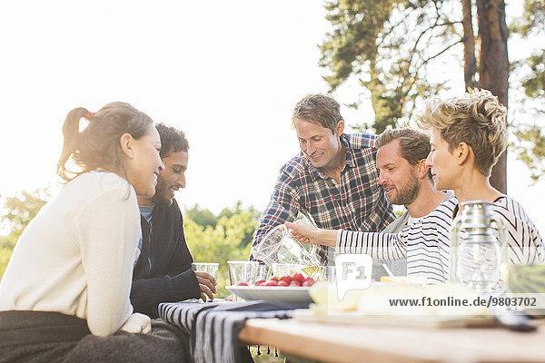 Freunde beim Mittagessen am Picknicktisch bei klarem Himmel