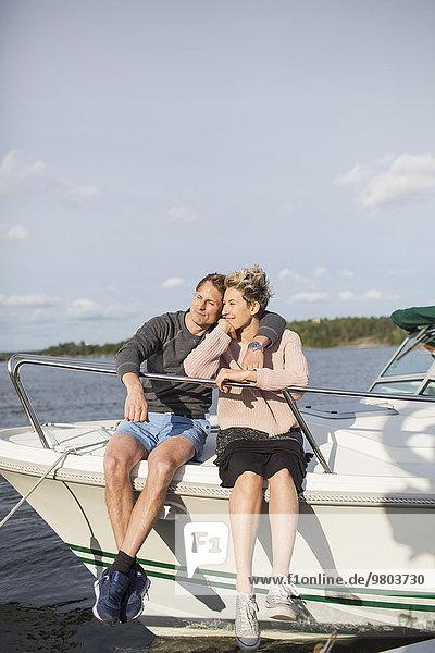 Liebespaar auf der Yacht gegen den Himmel sitzend