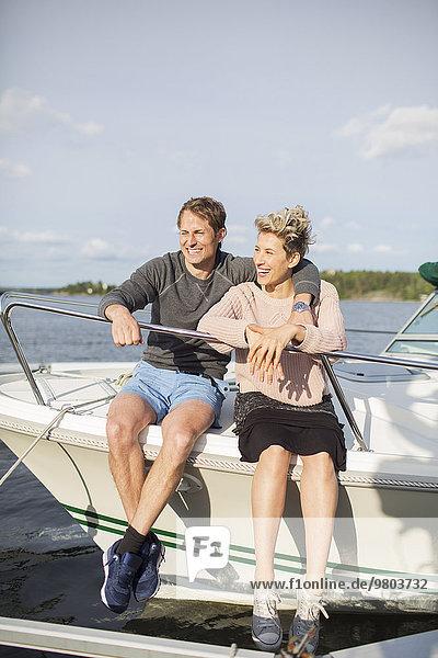 Glückliches Paar auf der Yacht gegen den Himmel sitzend