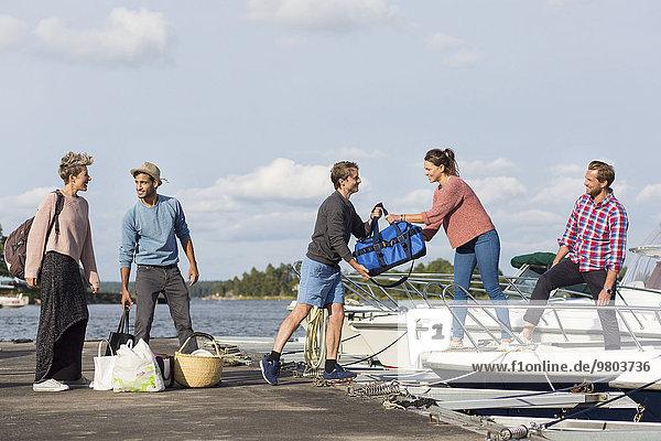 Gruppe von Freunden an Bord einer Yacht im Hafen gegen den Himmel