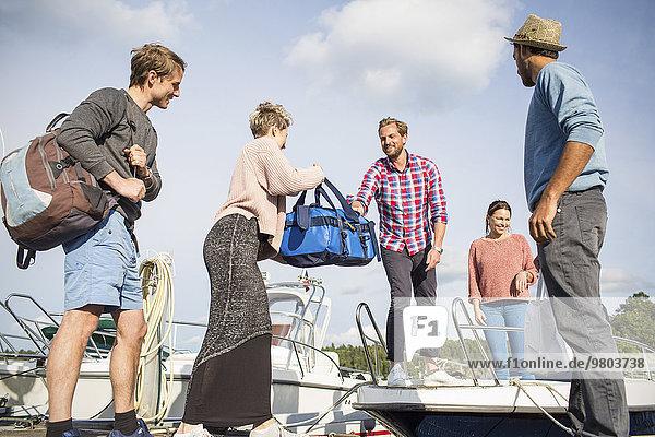 Frau übergibt Tasche an Freund auf der Yacht
