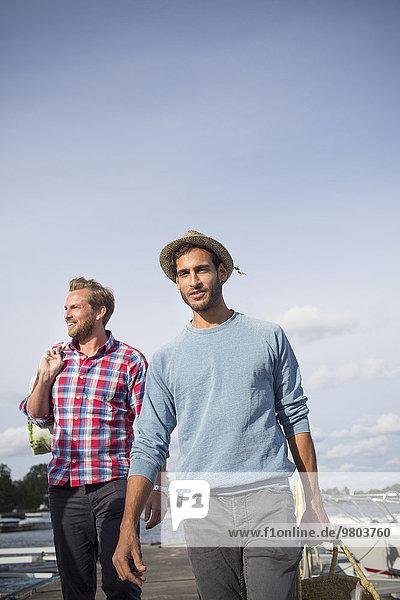Porträt eines Mannes mit Picknickkorb beim Spaziergang mit einem Freund am Pier