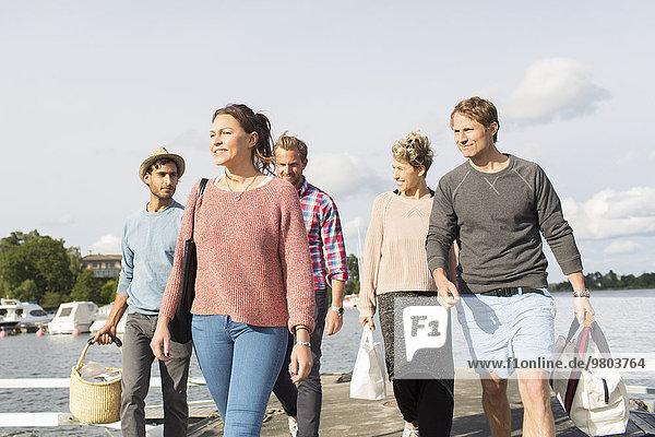 Gruppe von Freunden beim gemeinsamen Spaziergang am Pier