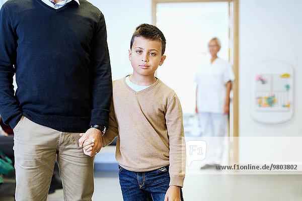 Porträt eines Jungen mit Vaterhand und Krankenschwester im Hintergrund in der Orthopädischen Klinik