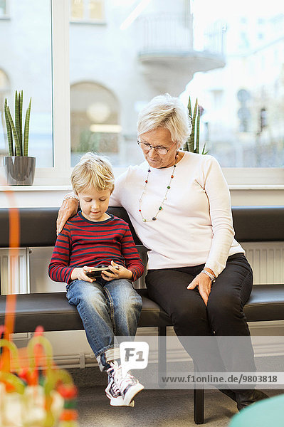 Großmutter und Enkel mit Smartphone im Wartezimmer der Orthopädischen Klinik