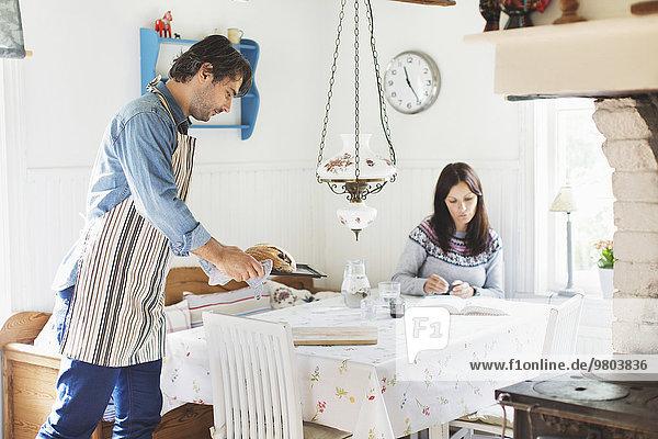 Seitenansicht des Mannes mit Brot auf dem Esstisch für die Frau zu Hause