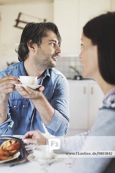 Mittlerer Erwachsener Mann beim Kaffee mit Frau am Frühstückstisch