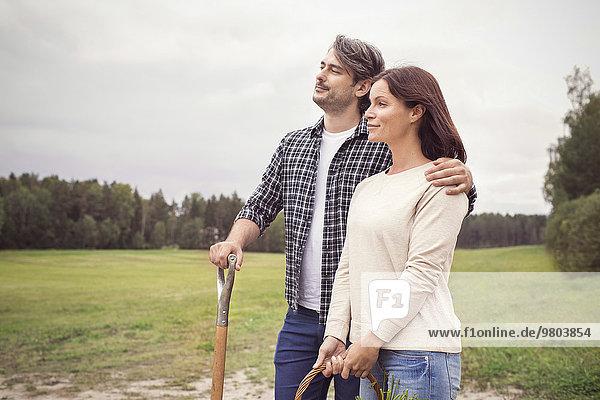 Nachdenkliches  mittleres erwachsenes Paar  das auf einem Bio-Bauernhof steht.