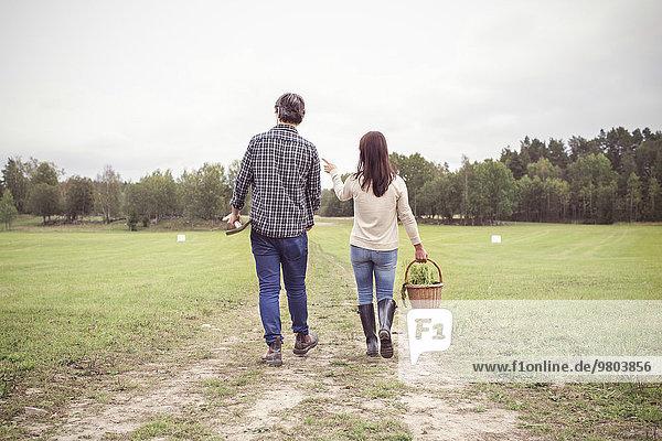 Durchgehende Rückansicht des Paares mit Korb und Gartengerät auf dem Feld