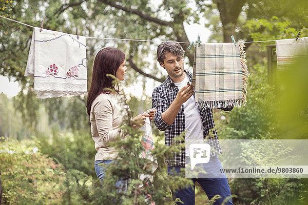 Pärchengespräch beim Wäschetrocknen im Hof