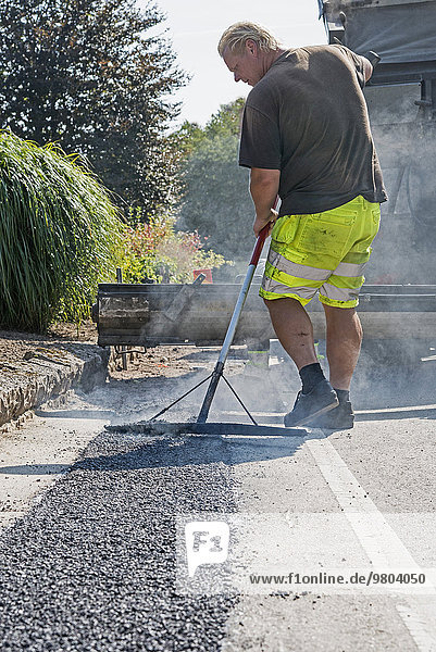 Rear view of construction worker laying tarmac on road