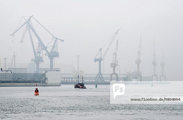 Kräne am Handelshafen bei nebligem Wetter