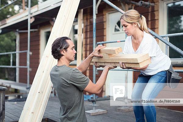 Seitenansicht des Paares  das den Holzstapel außerhalb des zu renovierenden Hauses trägt.