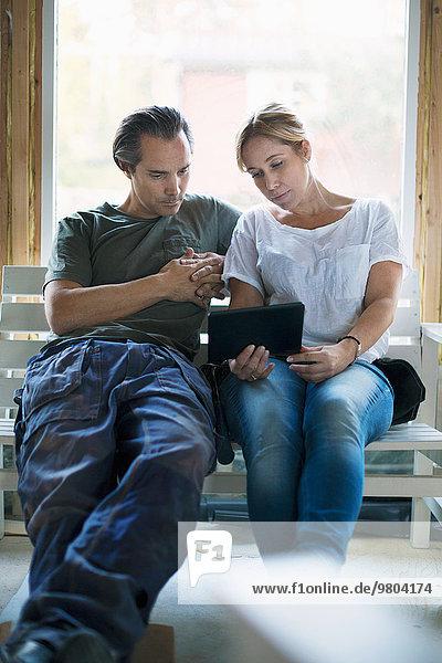 Paar mit Tablet-Computer im Haus in der Renovierung