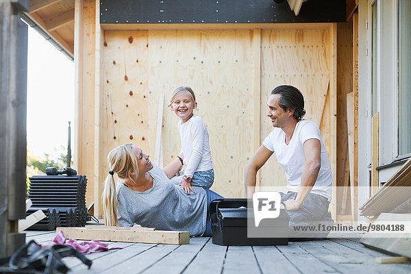 Glückliche Familie mit Werkzeugkasten vor dem Haus