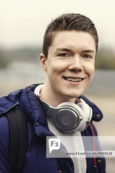 Porträt eines glücklichen Studenten mit Kopfhörer um den Hals im Freien