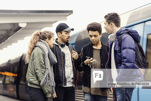 Multi-ethnische Universitätsstudenten mit Smartphone in der U-Bahn-Station