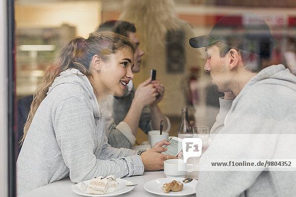 Blick auf ein junges Paar beim Telefonieren im Cafe durchs Glas