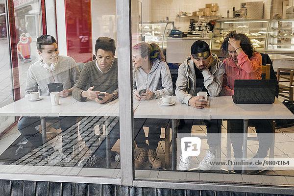 Multiethnische Freunde  die Technologien bei Tisch in der Cafeteria nutzen