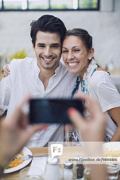 Freund fotografiert Paar durch Smartphone im Cafe