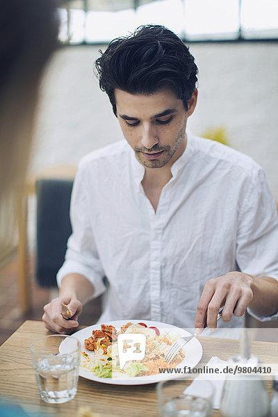 Mann beim Mittagessen mit Freund im Cafe