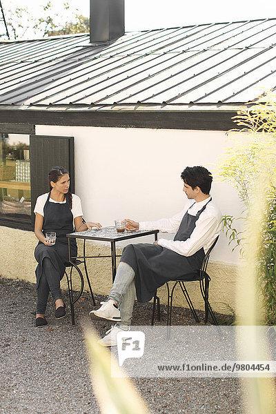 Kellnerin und Kellnerin bei der Kaffeepause vor dem Restaurant