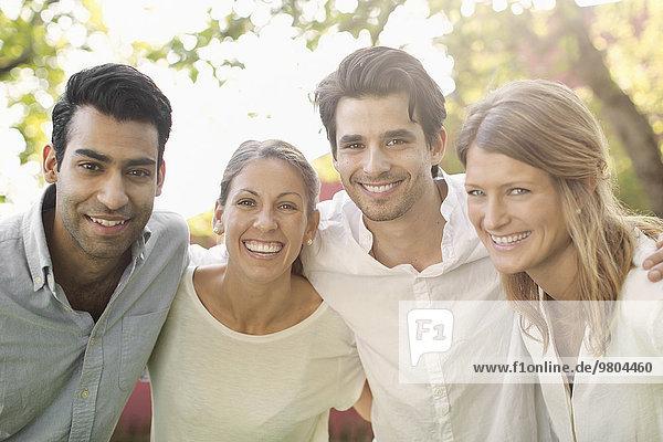 Porträt von vier glücklichen Menschen im Freien