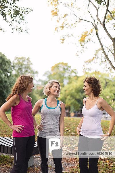 Fröhliche Frauen  die sich im Park unterhalten.