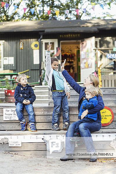Fröhliche Lehrerin gibt High-Five außerhalb des Vorschulgebäudes Fröhliche Lehrerin gibt High-Five außerhalb des Vorschulgebäudes