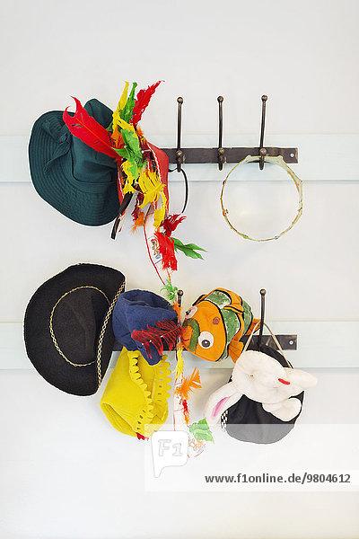 Spielzeug und Hüte am Haken im Kindergarten