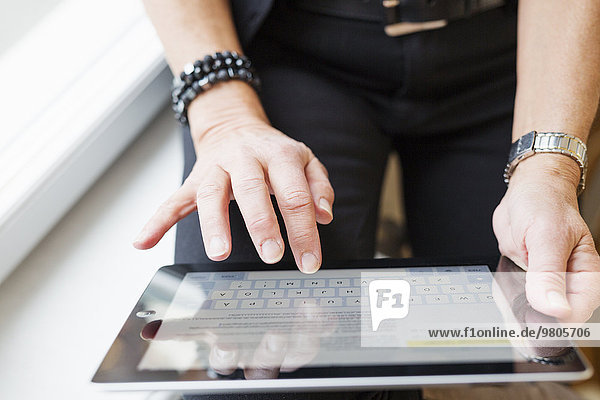 Midsection of businesswoman using digital tablet while sitting on window sill in office