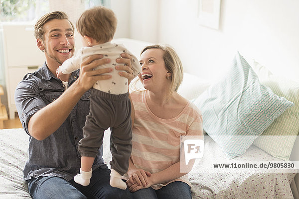 Fröhlichkeit Sohn klein Menschliche Eltern Bett spielen