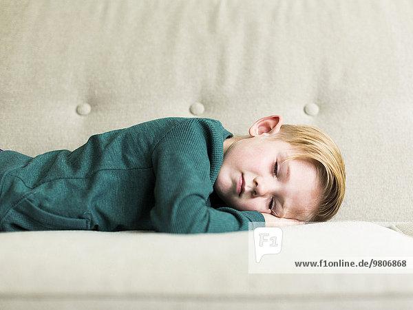 Boy (2-3) sleeping on sofa