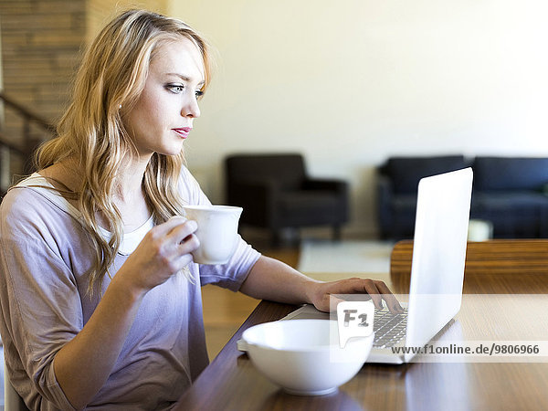 junge Frau junge Frauen benutzen Notebook trinken Kaffee Tisch